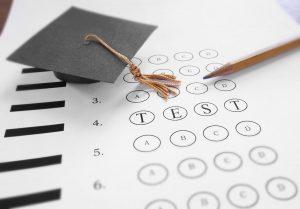 Mini mortar board graduation cap and Test text on multiple choice exam